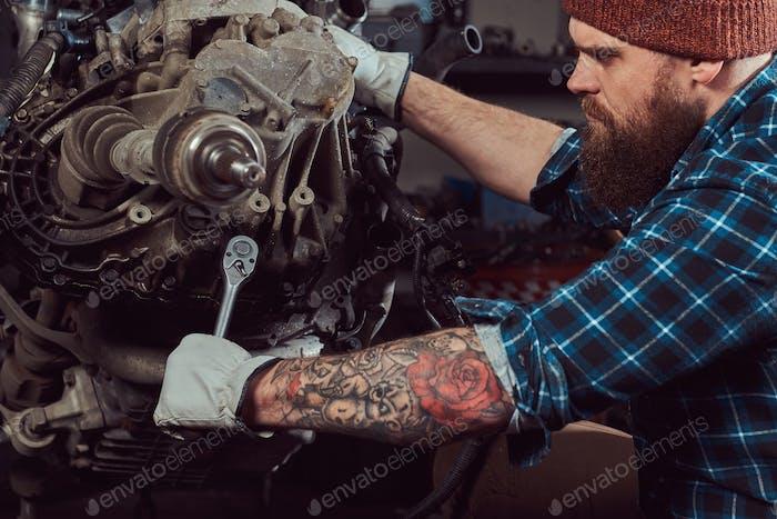 Brutal tätowierte Mechaniker repariert den Automotor in der Garage. Tankstelle.