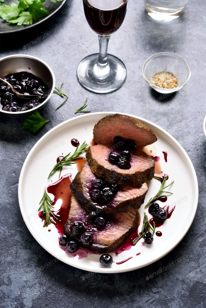 Sliced grilled beef with blueberry sauce
