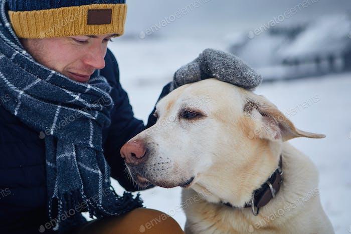 Man in warm clothing stroking dog on snowy field