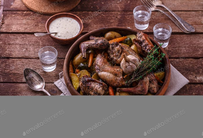 Rabbit baked with potatoe and herbs in a pot, copy space