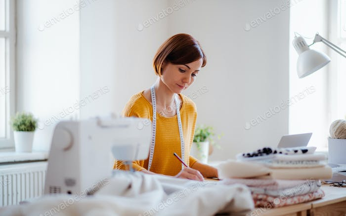 Young creative woman in a studio, startup of small tailoring business.