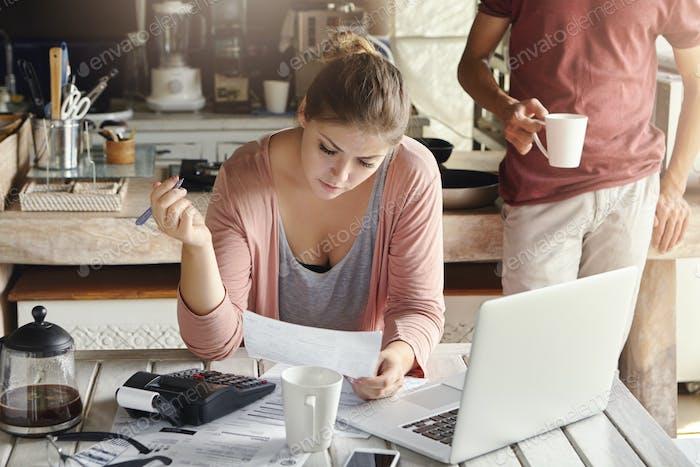 Schöne junge Frau, die das Inlandsbudget plant, die Familienausgaben abschneidet und versucht, etwas zu sparen