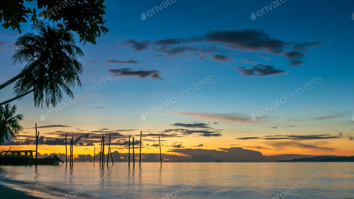 Sunset on Kri Island. Boats under Palmtrees. Raja Ampat, Indonesia, West Papua