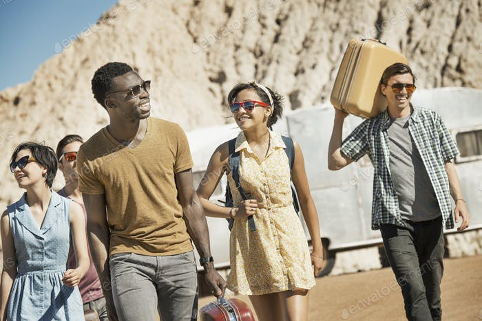 A group of people walking in a line in open desert country, carrying their cases, on a road trip.
