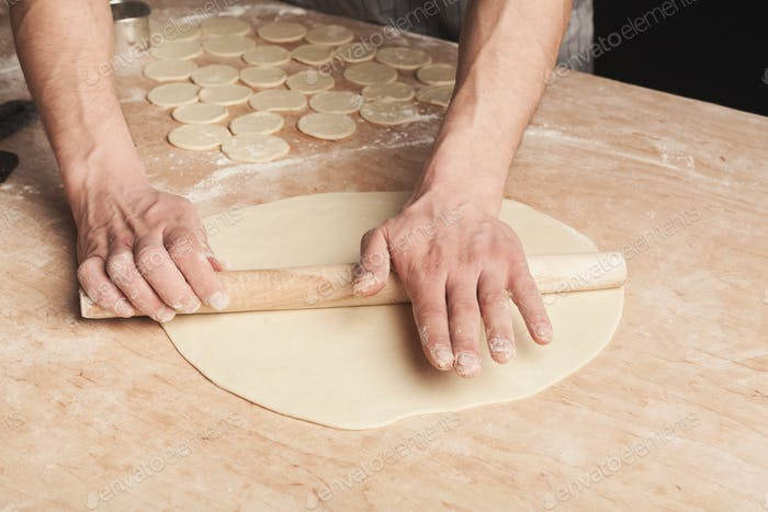 Preparing dumplings with meat, rolling out dough