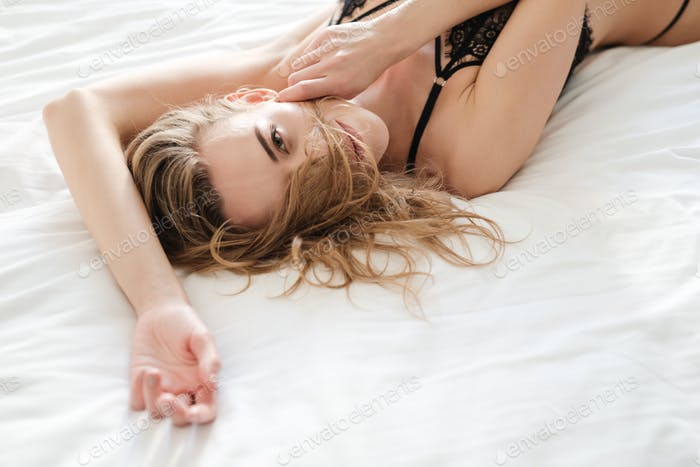 Sexy woman lies on bed indoors dressed in lingerie.