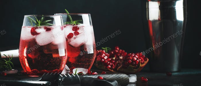 Red cocktail with cold vodka and pomegranate juice, ice cubes and rosemary