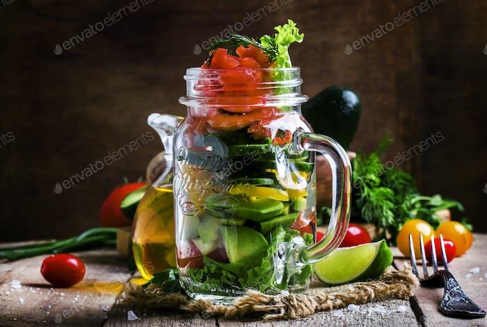 Salat mit Gemüse und Fisch, in einem Glas serviert