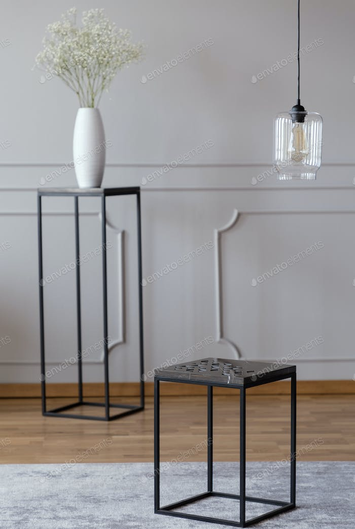 Metal end table standing on carpet in real photo of bright room