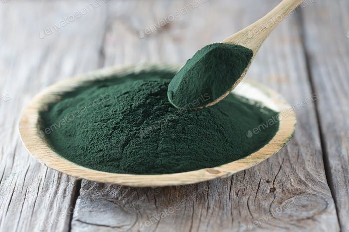 Chlorella single celled green algae. Detox superfood on the wooden plate