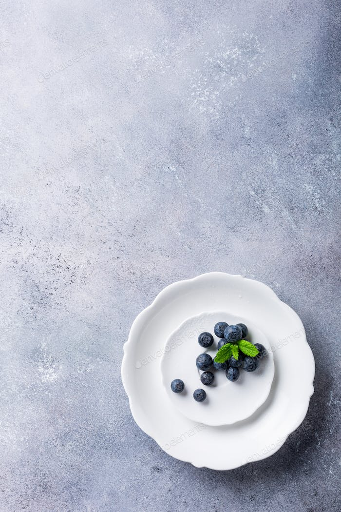 Freshly picked blueberries on white plate