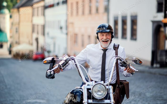 A senior businessman with motorbike in town, looking at camera.