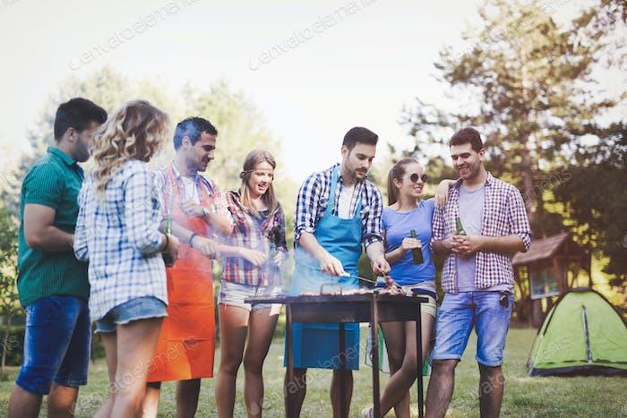 Glückliche Leute mit Camping und Grillparty