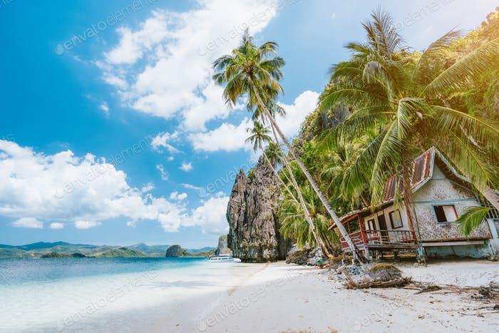 Vacation holiday on Palawan - El Nido island hopping tour. Lonely deserted hut under palm trees