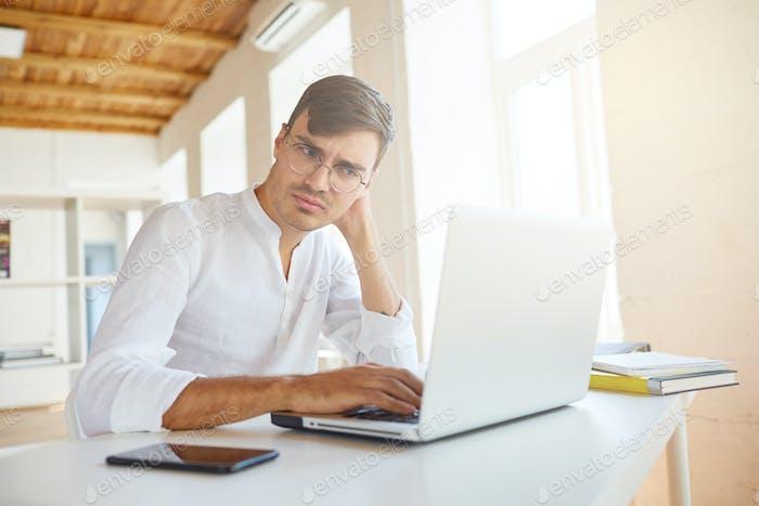 Closeup of thoughtful serious young businessman wears white shirt