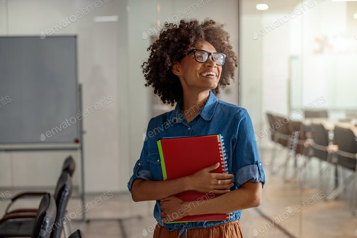 Pretty young woman in glasses standing with folder