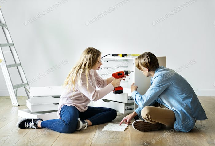 Woman using electronic drill install cabinet
