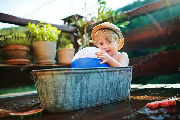 Small boy with a ball in bath outdoors in garden in summer, playing in water.