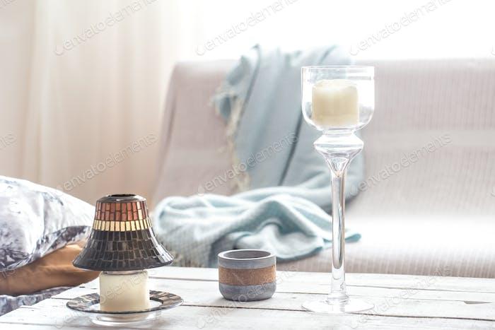 Schöne brennende Kerzen mit Flaschen auf weißem Tisch