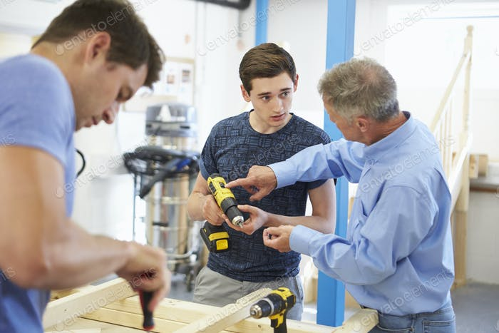 Teacher Helping College Student Studying Carpentry