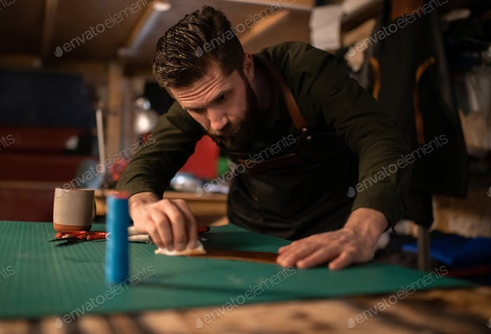 Focused craftsman smearing liquid on piece of leather