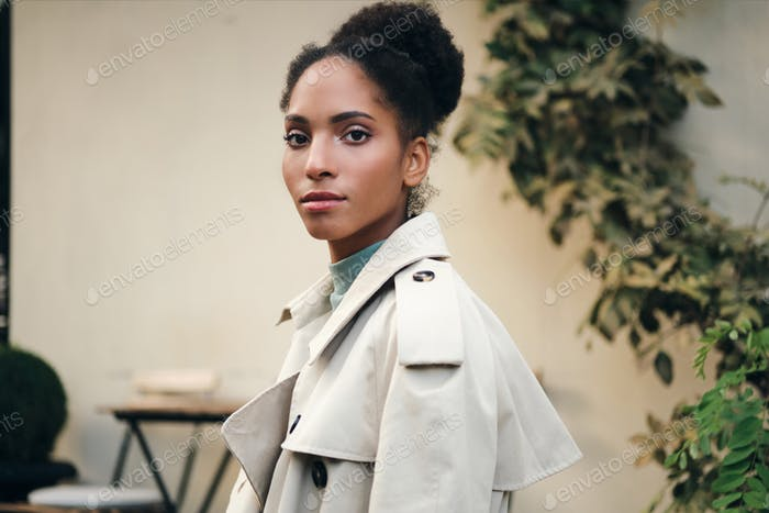 Beautiful African American girl in stylish trench coat confidently looking in camera on street