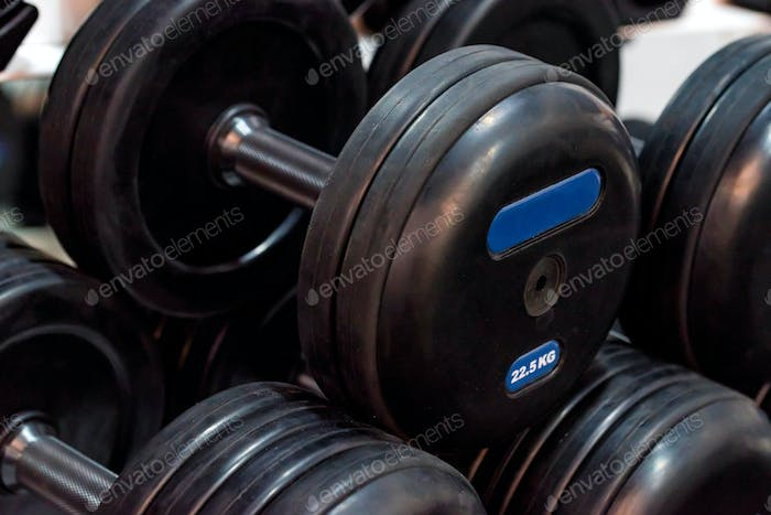 Closeup image of several black chrome dumbbells
