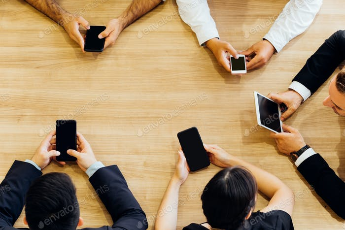 From above of business people using smartphones