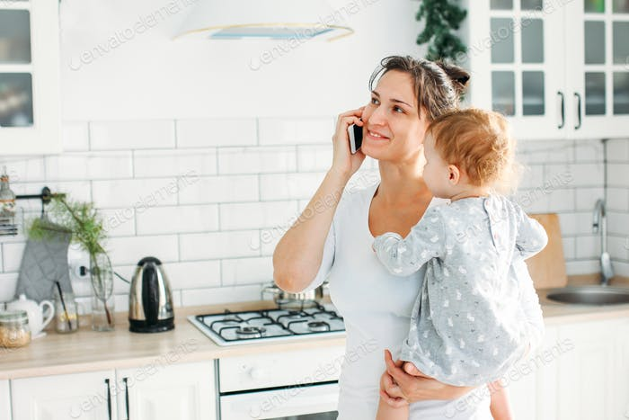 Young woman mom with baby girl on hands using mobile on bright kitchen