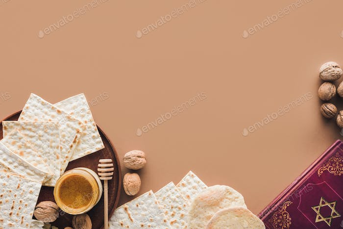 top view of traditional book with text in hebrew and matza with honey on brown surface