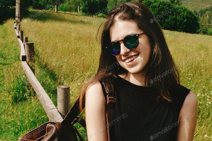 Иtylish Hipster Frau sitzend und lächelnd auf die Berge Blick