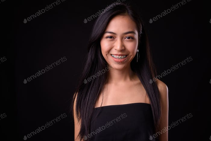 Face of happy young beautiful Asian woman smiling