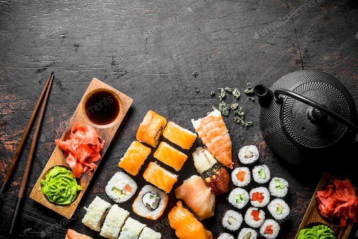 Verschiedene Arten von japanischem Sushi, Brötchen und Maki mit Sauce, Wasabi und grünem Tee in einer Teekanne.