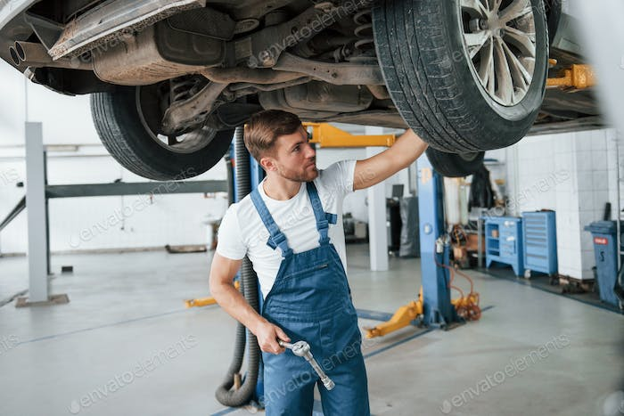 Unusual problem. Employee in the blue colored uniform works in the automobile salon