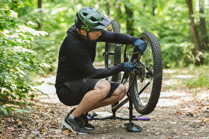 Young bicyclist fixing bike chain in forest