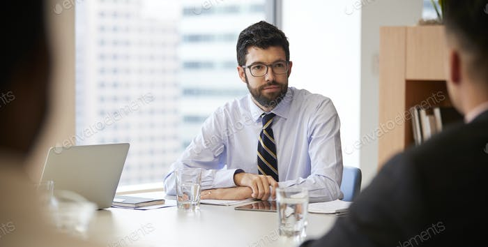 Businessman With Digital Tablet Sitting At Table Meeting With Colleagues In Modern Office