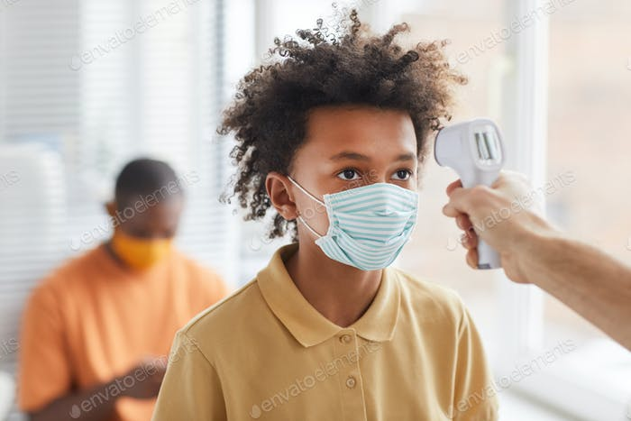 Doctor Checking Temperature of African-American Boy