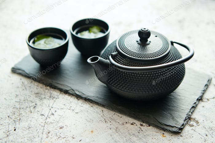Traditional eastern metal teapot and iron cups