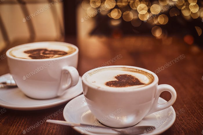 Zwei Tassen heißen Kaffee auf dem Holztisch in einem Café, Unschärfe Hintergrund mit Bokeh Effekt