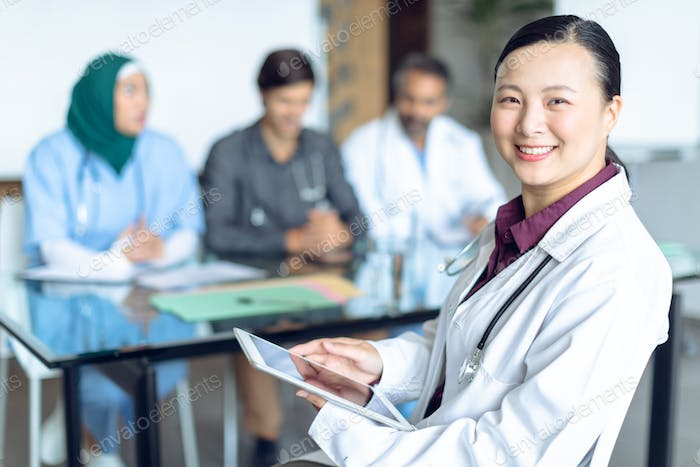 Happy Asian female doctor looking at camera while using digital tablet in the hospital.