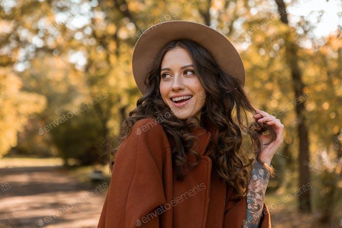 atractiva mujer elegante caminando en el parque vestido con abrigo marrón cálido