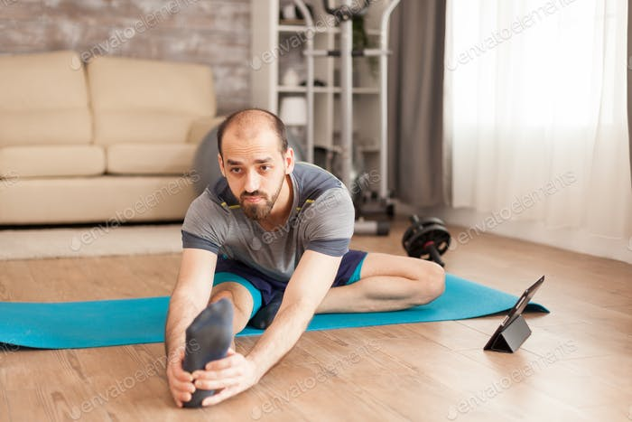 Man with healthy body doing legs stretching