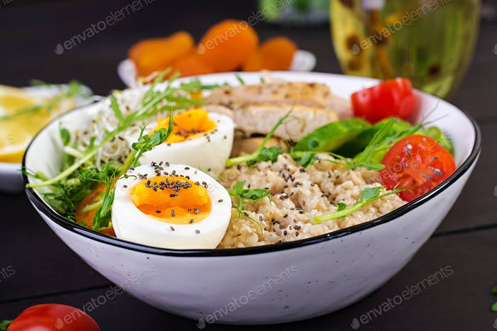 Healthy salad in a white bowl, chopsticks. Chicken rolls, rice, chuka and green onion.