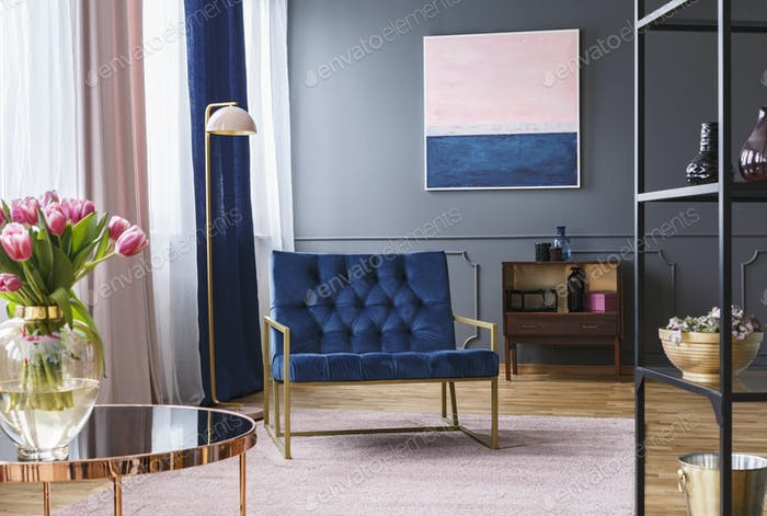 Navy blue armchair next to lamp in sophisticated apartment inter