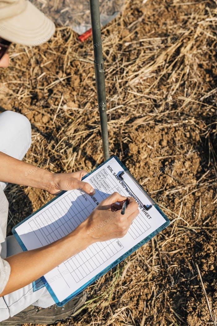 Soil Test. Female Agronomist Taking Notes In The Field