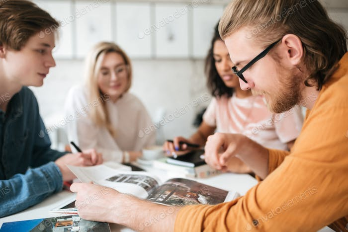 Young man with blond hair and beard thoughtfully looking in magazine with friends on background