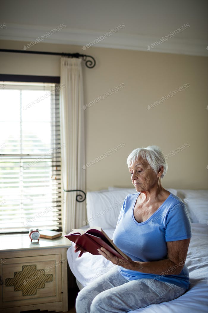 Senior woman reading a book in the bedroom