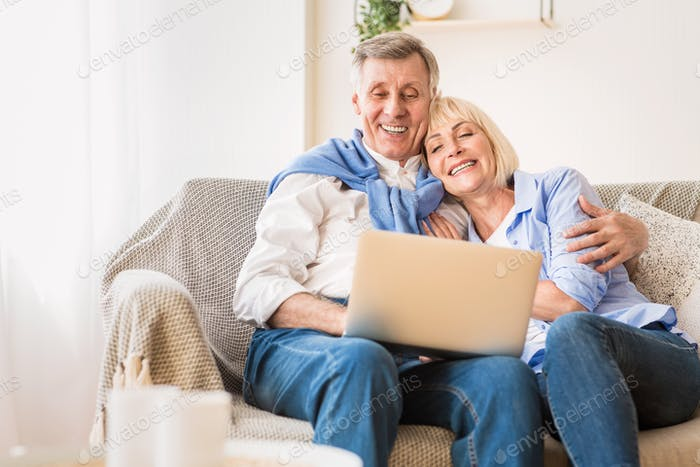 Loving mature couple watching film on laptop computer