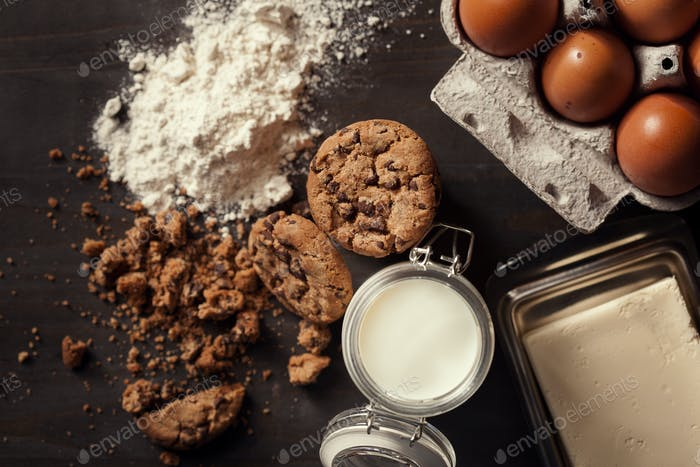 Flat lay of Homemade chocolate chip cookies with bottle of milk, white flour, fresh eggs,butter and