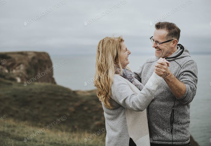Romantic senior couple dancing on a hill